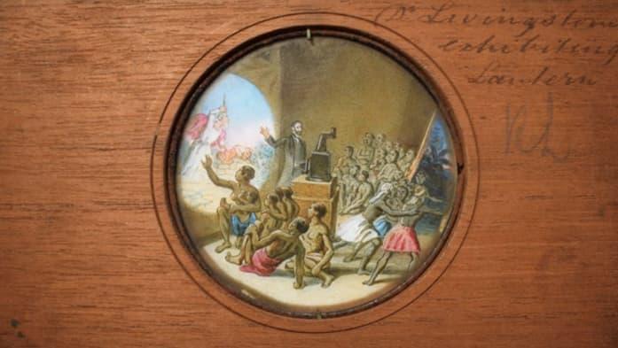 Lantern slide depicting David Livingstone using a magic lantern